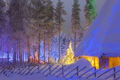 Travel Concepts and Ideas. Marvelous Lapland Houses in Suomi Village. In Front of Marvelous Highlighted Winter Forest Scenery.Horizontal Image Royalty Free Stock Images