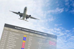 Travel conceptual. Airplane flying over an information board against blue cloudy sky Royalty Free Stock Images