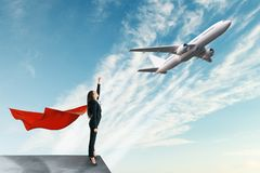 Travel and confidence concept. Superhero businesswoman looking at flying by airplane. Travel and confidence concept stock image