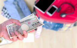 Travel cost, hand woman with Japanese currency yen bank notes on. Travel accessories background Royalty Free Stock Image