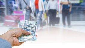 Travel cost, hand woman with Japanese currency yen bank notes on. Blurred background travelers walking with a luggage at airport terminal Stock Photo