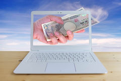 Travel cost, hand woman with Japanese currency yen bank notes with modern laptop. On wood desk with blue sky background Stock Images