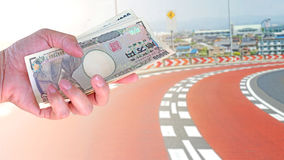 Travel cost, hand woman with Japanese currency yen bank notes on. Vehicles run on mountain road at Japan background Stock Photos