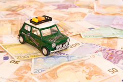 Travel costs. Toy-car placed on lots of banknotes Royalty Free Stock Photo
