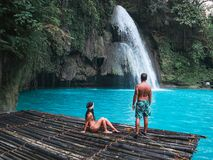 Free Travel Couple Alone On The Bamboo Raft Of Turquoise Water Of Kawasan Falls In Cebu Royalty Free Stock Photo - 159089635