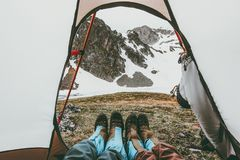 Travel couple feet mountains view from tent camping entrance. Lifestyle concept adventure vacations outdoor Stock Image