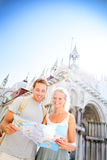 Travel couple reading map on in Venice, Italy. On Piazza San Marco in front of Saint Mark's Basilica. Happy young couple on travel vacation in Europe. Happy royalty free stock photography
