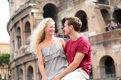 Travel couple in Rome by Coliseum in love. Tourists dating laughing having fun. Two happy young tourist traveling in Italy. Beautiful blonde women and men in royalty free stock image