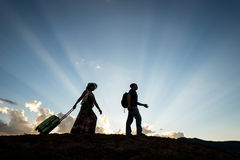 Travel couple silhouette. Man and women travel on sunset blue sky dusk stock images
