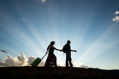 Travel couple silhouette. Man and women travel on sunset blue sky dusk royalty free stock images