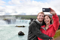 Travel couple taking phone selfie photo in Iceland. Selfie couple taking smartphone picture of Godafoss waterfall outdoors on Iceland. Couple visiting famous stock photo