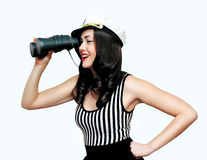 Travel, cruise, people concept - pretty smiling woman brunette sailor looking through binoculars. Pin-up style over white background royalty free stock photography