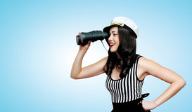 Travel, cruise, sea and people concept - pretty smiling woman. Brunette of a sailor looking through binoculars, pin-up style stock photography