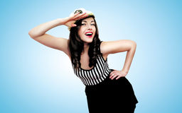 Travel, cruise, sea and people concept - pretty smiling woman. Brunette of a sailor saluted in pin-up style royalty free stock images