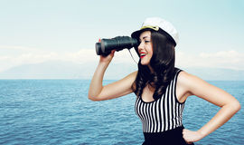 Travel, cruise, tourism and people concept - pretty woman. Travel, cruise, tourism and people concept - pretty smiling woman of a sailor looking through royalty free stock photos