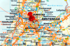 Travel destination Amsterdam. Closeup of a road map with pin point destination and blurred surroundings Royalty Free Stock Photography
