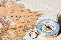 Travel destination Brazil, ancient map with vintage compass. Compass on a map pointing at Brazil, planning a travel destination Stock Image