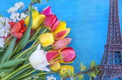 Travel destination concept: Paris. Effel tower and bouquet of multicolored tulips on bright blue wooden background Stock Photography