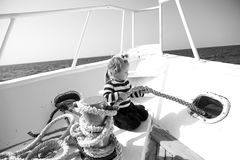 Travel destination, cruise, travelling. Child pull rope on yacht on sunny day. Adventure, discovery, wanderlust. Summer vacation concept. Boy in sailor shirt Royalty Free Stock Photo