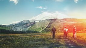Travel Destination Experience Lifestyle Concept concept. Team of travelers with backpacks and trekking sticks climbs the mountain. Hiking Team Goes To Mount royalty free stock image