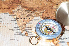 Travel destination India, ancient map with vintage compass. Compass on a map pointing at India, planning a travel destination Stock Photography