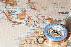 Travel destination Indonesia, ancient map with vintage compass. Compass on a map pointing at Indonesia, planning a travel destination stock photo