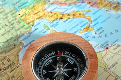 Travel destination Italy, compass with a map on the background. Compass on a map pointing at Italy on the background and planning a travel destination Stock Images