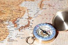 Travel destination Japan, ancient map with vintage compass. Compass on a map pointing at Japan, planning a travel destination royalty free stock images