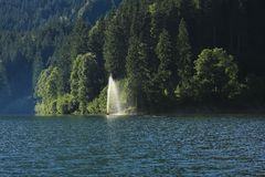 Travel destination lake Obersee. Firs and fountain Royalty Free Stock Image