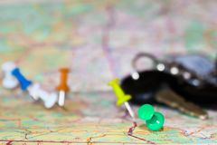 Travel destination points on a map indicated with colorful thumbtacks and shallow depth of field with space for copy. The keys to. The car in the blur in the Royalty Free Stock Photos