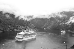 Travel destination, tourism. Cruise ship in norwegian fjord. Passenger liner docked in port. Adventure, discovery. Geiranger, Norway - January 25, 2010: travel royalty free stock images