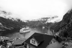 Travel destination, tourism. Ship in norwegian fjord on cloudy sky. Ocean liner in village harbor. Travel destination. Geiranger, Norway - January 25, 2010 royalty free stock photos