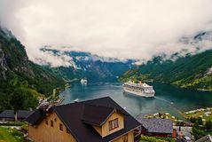 Travel destination, tourism. Ship in norwegian fjord on cloudy sky. Ocean liner in village harbor. Travel destination. Geiranger, Norway - January 25, 2010 stock image