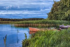 Travel destinations concepts. Peaceful picturesque landscape. Of The Strusto Lake with Wooden Boat at Foreground. Lake is a Part of National Braslav Lakes Stock Photos