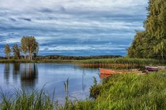 Travel destinations concepts. Peaceful picturesque landscape of. The Strusto Lake with Wooden Boat at Foreground. Lake is a Part of National Braslav Lakes Royalty Free Stock Images