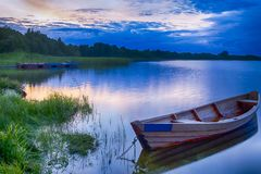 Travel destinations concepts. Tranquil and peaceful picturesque. Landscape of The Strusto Lake with Wooden Boat at Foreground. Lake is a Part of National Royalty Free Stock Photo