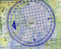 Travel Dreams. Image of a plastic compass with a map in the background Stock Photography