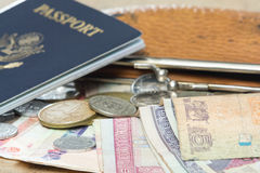 Travel essentials. Travel documents and different international currencies on a counter top Royalty Free Stock Photography