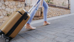 Travel through Europe. A woman carries a bag on wheels on the narrow street of the old town. Only the legs and a bag stock footage