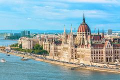 Travel and european tourism concept. Parliament and riverside in Budapest Hungary with sightseeing ships during summer day with bl royalty free stock photography