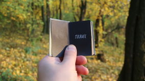 Travel explore wanderlust or trip adventure idea. Hand holding a book with the inscription Travel stock footage
