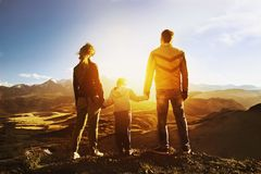 Travel family concept mountains sunset. Travel concept. Family standing on mountains backdrop and looking at sunset Stock Image