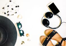 Travel female accessories phone, earphones, sunglasses, sandals, necklace and hat on white background royalty free stock photo