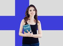 Travel in Finland and learn finnish language. Happy smiling woman holding phrasebook against the Finnish flag background.  royalty free stock images