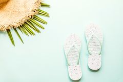 Travel flat lay items: beach slippers, straw hat and palm leaf. Place for text. Top view. Summer concept royalty free stock photography