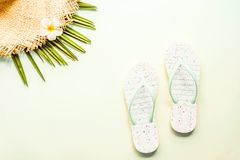 Travel flat lay items: beach slippers, straw hat and palm leaf. Place for text. Top view. Summer concept royalty free stock photo