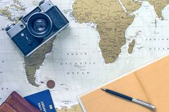Travel flatlay with wallet, pocketbook, passport, pen and camera on world map stock image
