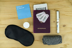 Travel and flight still life concept. With a passport, tickets, sleeping mask, pen, cream and boarding pass laid out on a wooden desk viewed from above Stock Photo