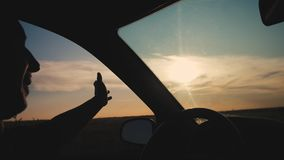 Travel freedom concept. Slow motion video. Drivers hand plays with the sun from a car window on a background of a stock footage