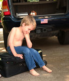 Frustrated Child Sitting on Suitcase. Boy appears frustrated as he tries to close a suitcase Stock Images